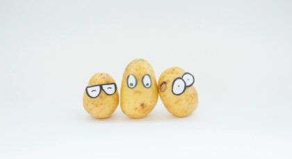 Three potatoes with funny looking eyes drawn on them