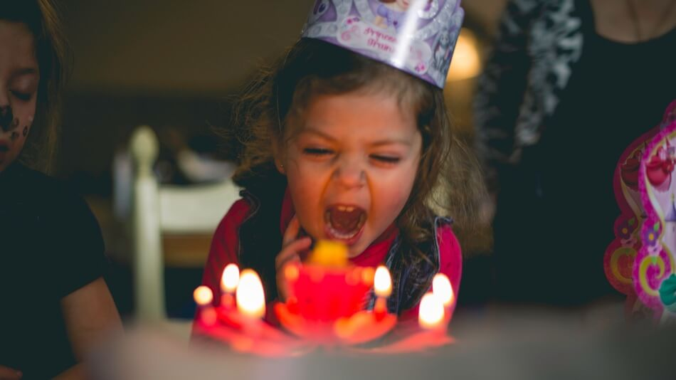 Girl blowing out candles after being told birthday puns and jokes