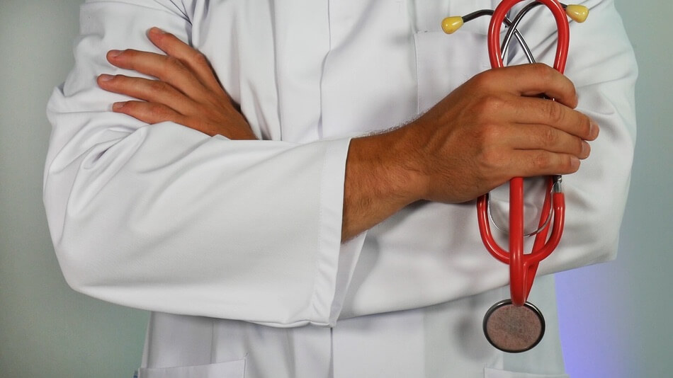 Doctor holding a stethoscope thinking of doctor jokes and puns